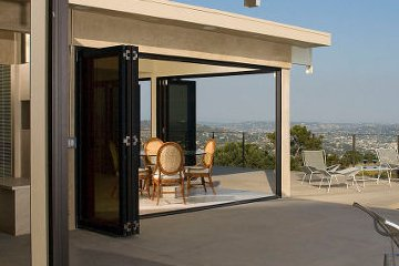 Open and Airy Design accordian patio doors. In a hilltop home overlooking the city below.