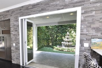 Small Backyard with Outdoor Water Fountain opened up with bi-folding door. Monocromatic Kitchen Design.