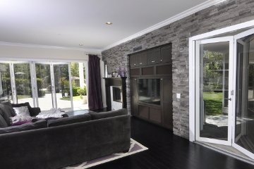 Built in TV stand in open living room with large glass wall openings dark color scheme.