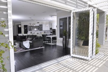 White Kitchen open floorplan with lowe glass accordian doors and dark couch. White black modern design.