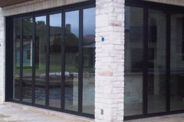 Outdoor Brick Landscaping with two bi-folding doors meeting at a corner.  Stone paver floors and stairs.