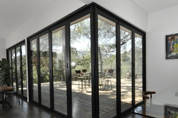 Black Aluminum corner door system minimalist design seamless transition to the outside patio dark wood floors.