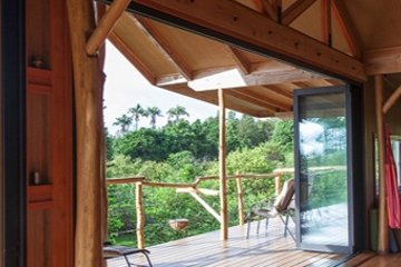 Forest cabin with large movable glass walls natural wooden deck rails Dhyana meditation cushion zen design.