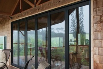 studio loft with movable glass wall made with folding accordian bifold doors. Naturalist Style home. Lanai