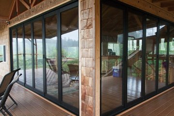 Forest home with black aluminum retractable doors that make studio open and airy.