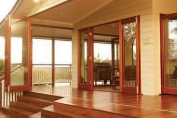 Raised wooden porch with large door openings with folding doors that open the house to the outdoors.