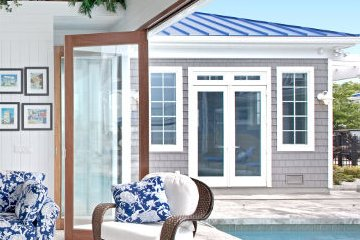 pool house with Blue accent print couch with white wicker chairs Aluminum Wood Clad folding doors.