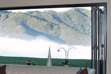 Morning fog hill top view white linen box couch with disappearing wall of glass doors.