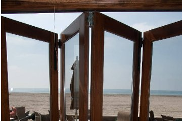 Beach house maximize ocean view outdoor dining patio set viewed through aluminum wood clad doors.