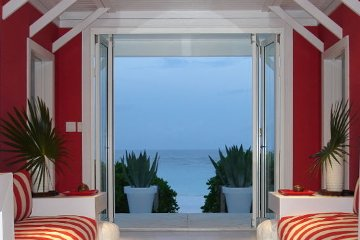 Sliding door leading to beach front propertly resort style livingroom. Red striped futon couch. Bloodred wall.