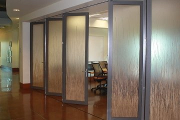 Airport executive lounge with movable glass wall. Gray Aluminum accordian bi-folding door. Privacy glass. ADA Compliant.