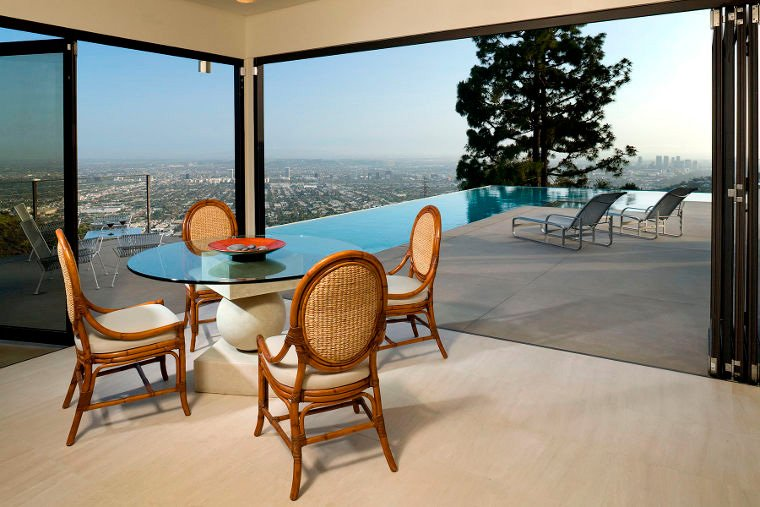 Lanai Doors Aluminum Folding Glass Doors open to patio with infinity pool and view of downtown Los Angeles
